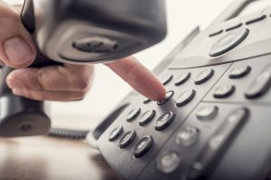 person-dialing-on-voip-phone